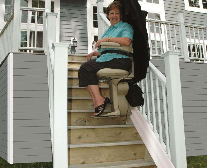 lady riding outdoor stair chair lift in backyard
