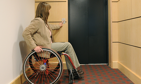 Handicapped woman using a Limited Use Limited Application Elevator