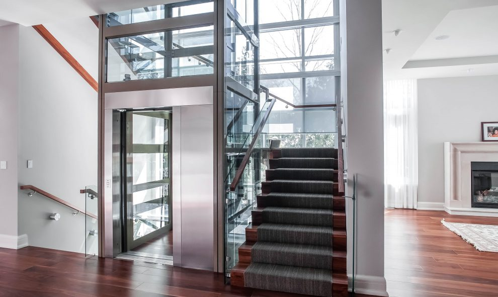 Glass elevator built into landing onto a luxury living area