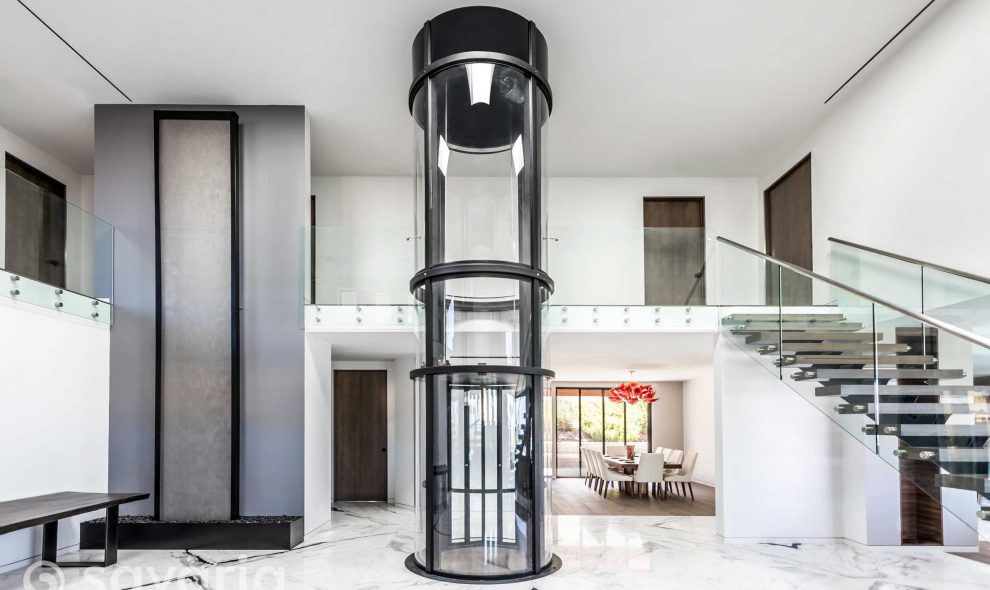 Round clear elevator in center of home entryway