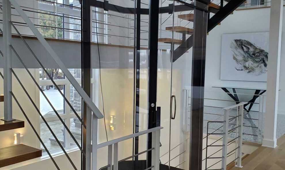 Octagonal glass elevator with black trim in luxury home