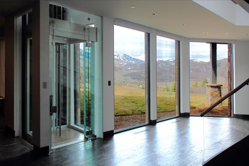 glass elevator next to a set of windows with scenic view.