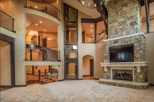 Glass elevator in large main living area of luxury home
