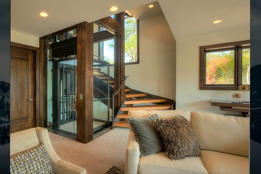 Glass elevator in luxury home from living area.